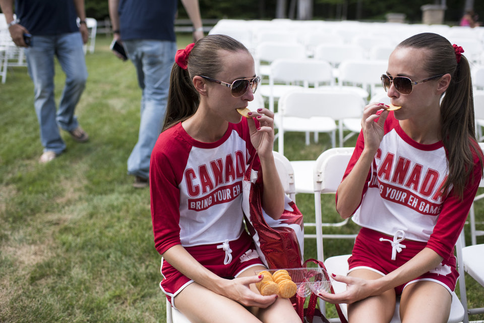 Allison, left, and Lauren Knight, 32 of Windsor, Ontario, share crackers with each other at the Twins Days Festival in Twinsberg, Ohio. Photo by Dustin Franz