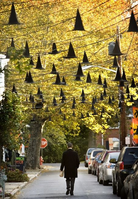 A local resident walks down Thompson Street in Bordentown City which is strung with floating witch hats for Halloween. The residents of the street traditionally go over the top decorating for Halloween with a particular theme each year lead by Thompson Street resident, artist and theatrical designer Frank Rios. Michael Mancuso/The Times (2 of 2)