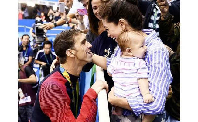 Michael Phelps conversa com a mulher, com filho no colo, após medalha de ouro durante a Rio 2016