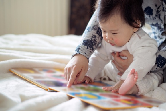 baby-girl-reading-book-with-mom-picture-id651973736
