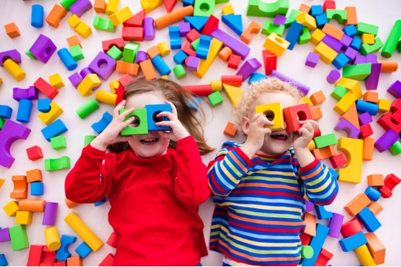 children-playing-with-colorful-blocks-building-a-block-tower-picture-id589961490