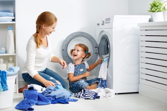 family-mother-and-child-girl-in-laundry-room-near-washing-machine-picture-id666384222