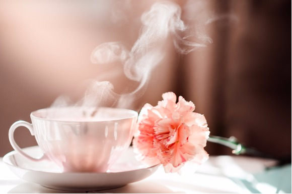 morning-coffee-tea-cup-with-steam-and-carnation-flower-picture-id617597890