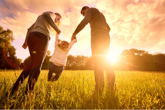 parents-hold-babys-hands-happy-family-in-park-evening-picture-id588959064