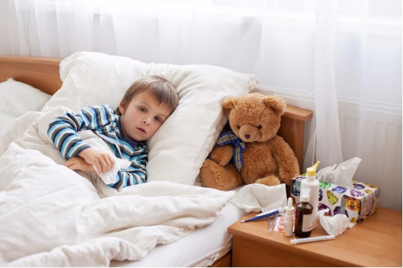 sick-child-boy-lying-in-bed-with-a-fever-resting-picture-id620408300