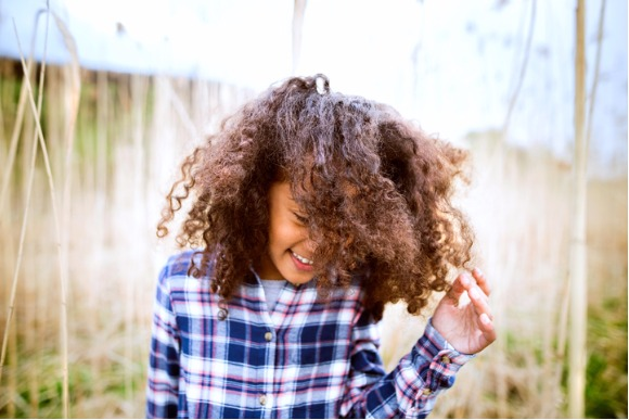 african-american-girl-in-checked-shirt-outdoors-in-field-picture-id849301600