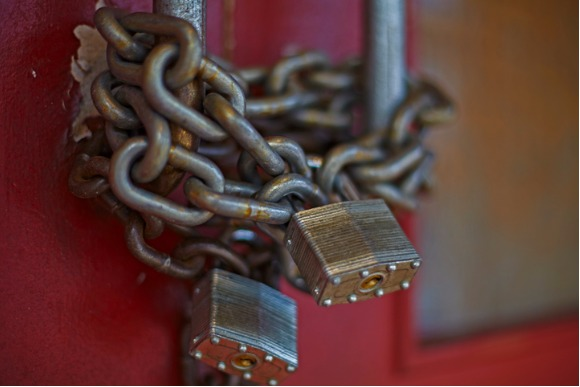 chain-and-locks-on-doors-of-closed-business-picture-id595351766