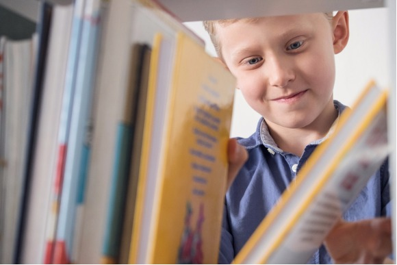 cute-little-boy-choose-a-book-on-the-bookshelf-picture-id500732748