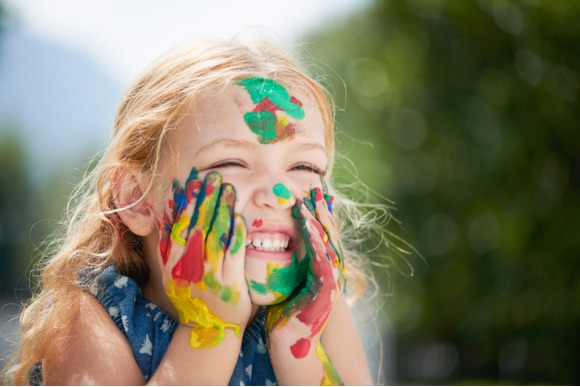 little-girl-child-painting-with-hands-on-face-oudoors-picture-id481536104