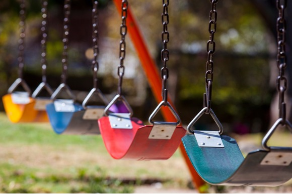 empty-colorful-swings-at-the-park-picture-id525027976