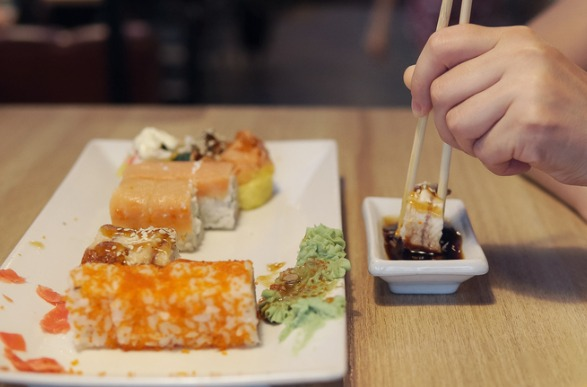 girl-eating-sushi-and-dip-in-sauce-in-sushi-bar-close-up-picture-id886482520