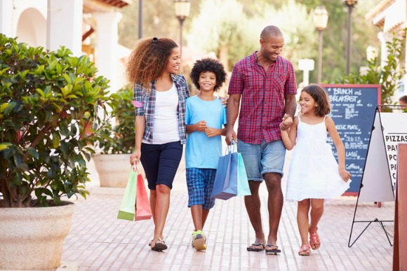 family-walking-along-street-with-shopping-bags-picture-id469197022