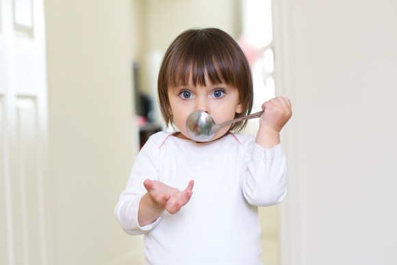 little-girl-with-spoon-in-mouth-picture-id516423951