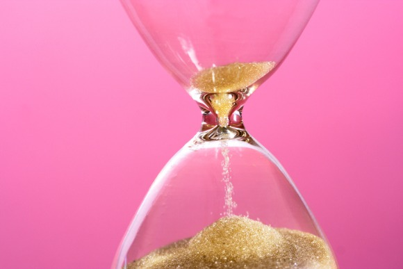 close-up-of-hourglass-against-pink-background-picture-id598792124