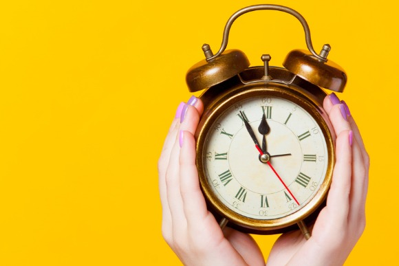 photo-of-female-hands-holding-alarm-clock-on-the-wonderful-yellow-picture-id677634644