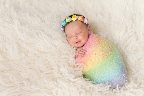 smiling-newborn-baby-girl-wearing-a-rainbow-colored-swaddle-picture-id485885456