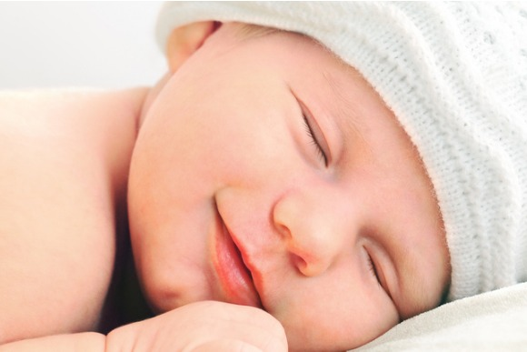 smiling-newborn-baby-in-white-hat-picture-id159449979