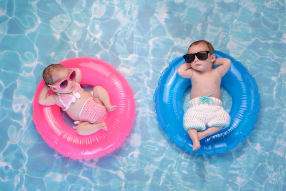 baby-twin-boy-and-girl-floating-on-swim-rings-picture-id628951466