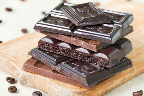 broken-chocolate-bars-of-different-kinds-of-chocolate-are-stacked-on-picture-id833999078