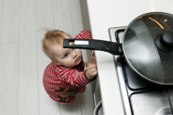 child-safety-at-home-concept-toddler-reaching-for-pan-on-the-stove-in-picture-id931131502