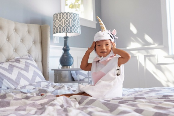 girl-dressed-in-unicorn-costume-sitting-on-bed-at-home-picture-id538043968