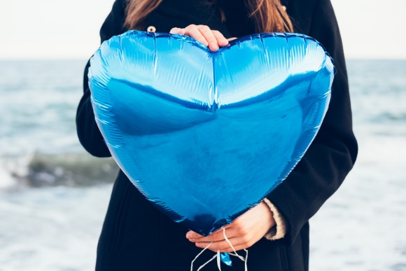 girl-in-black-coat-holding-a-blue-balloon-picture-id519712040