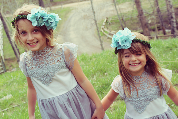 Two happy kids in nature and fancy dresses smile at the camera