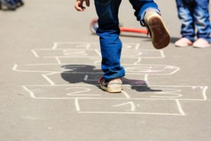 kids-playing-hopscotch-on-playground-outdoors-picture-id512047790
