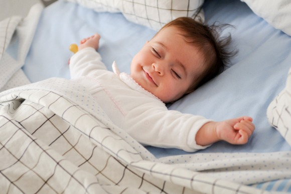 smiling-baby-girl-lying-on-a-bed-picture-id537627268