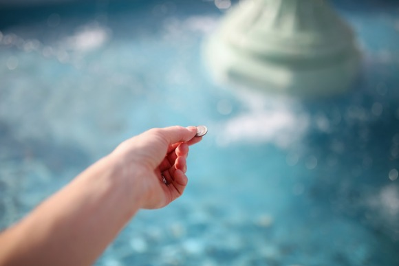 womans-hand-throwing-coin-in-wishing-fountain-picture-id809056542