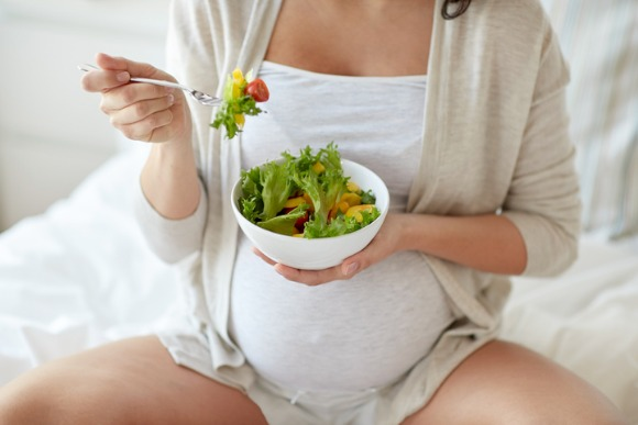 close-up-of-pregnant-woman-eating-salad-at-home-picture-id864581910
