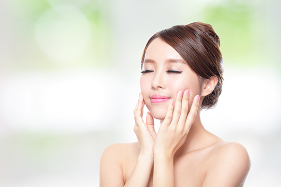 close up of attractive woman face relax closed eyes with nature green background, asian beauty