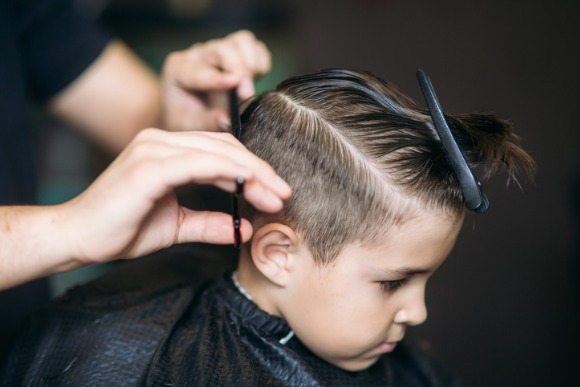 little-boy-getting-haircut-by-barber-while-sitting-in-chair-at-picture-id680907176