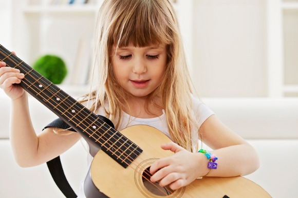 little-girl-playing-guitar-at-home-picture-id582310080