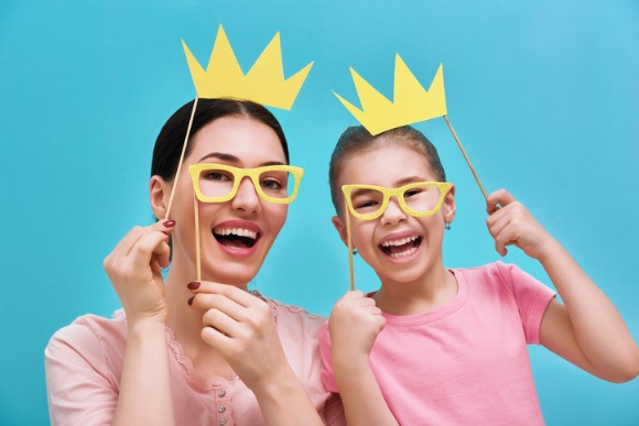 mom-and-child-are-holding-crowns-picture-id642242986
