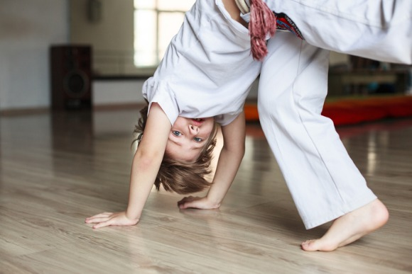 boy-practicing-capoeira-in-gym-picture-id604383448