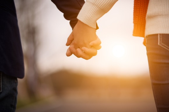 heterosexual-couple-holding-hands-and-walking-together-outdoors-picture-id641357926