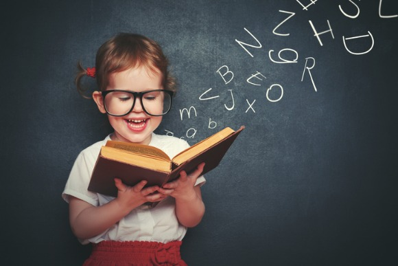 little-girl-with-glasses-reading-a-book-with-departing-letters-picture-id473466604