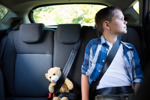 teenage-boy-sitting-with-teddy-bear-in-the-car-picture-id824815606
