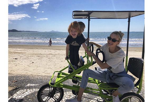 Carol Trentini e filhos Bento e Benoah pedalam pela orla da praia (Foto: Reprodução/ Instagram @carolinetrentini)