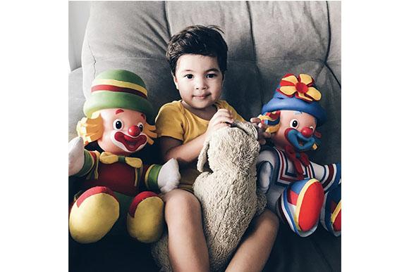 10h30 - Ele adora ver desenho animado no sofá rodeado dos seus brinquedos.(Foto: Reprodução/ Instagram @alinegoficial)