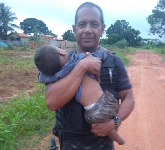 Policial segurando um dos irmãos | Foto: Reprodução / G1 / Gerência de Operações Especiais (GOE)