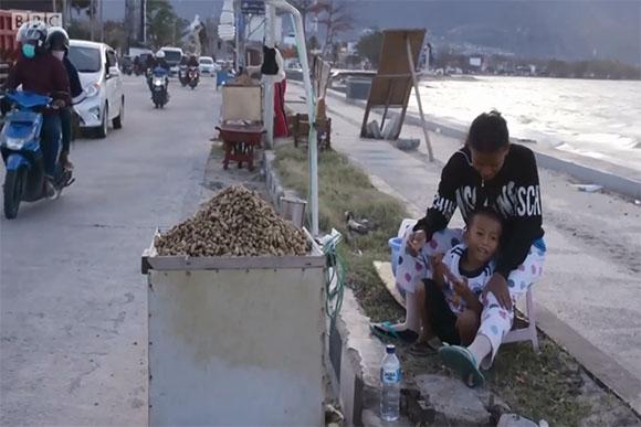Jumadil precisa voltar à praia todo dia para ajudar a mãe no trabalho (Foto: Reprodução/ BBC News)