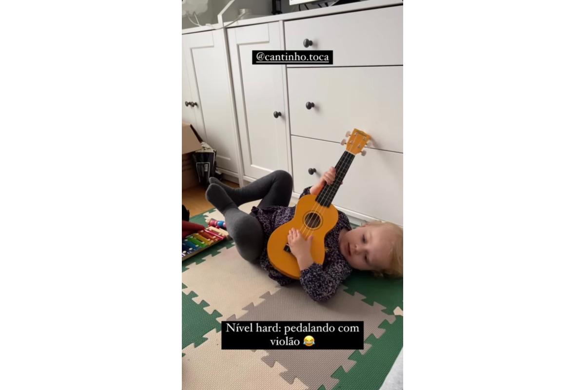 Alice aprendendo tocar violão