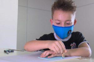 Menino faz máscaras para doar aos colegas
