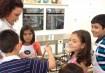 Helô explica às crianças que, para o brigadeiro ficar bom, é preciso mexer a mistura sem parar.