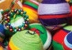 Quem tem jeito com as mãos pode fazer os enfeites, como estas bolas feitas de lã de tricô, supercoloridas e bonitas.